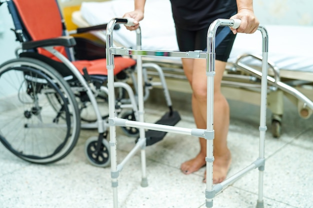 Asian middle-aged lady woman patient walk with walker at nursing hospital ward.