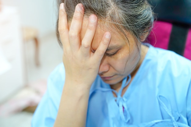 Asian middle-aged lady woman patient worry about sickness, headache and feel sad in the ho