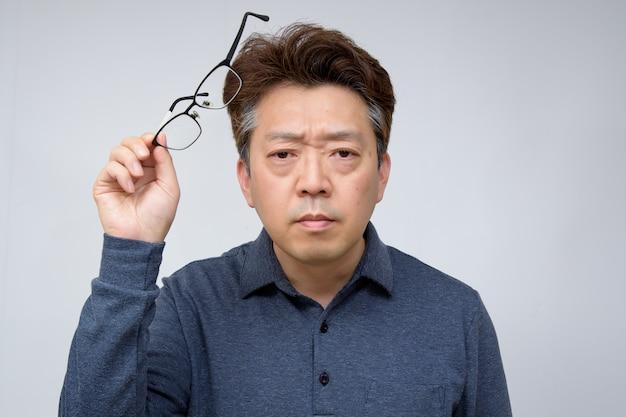Азиатский мужчина средних лет пытается снять очки и что-то увидеть. плохое зрение, пресбиопия, миопия.