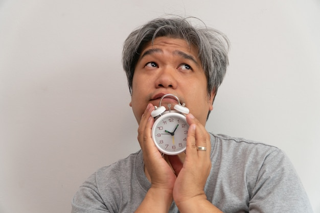 Asian middle-aged man is holding a white alarm clock and his face showed boredom and feeling bad, his problem is a sleep disorder.