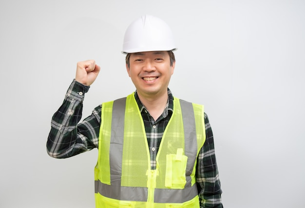 Asian middle-aged man in a light green work vest and white safety hat.