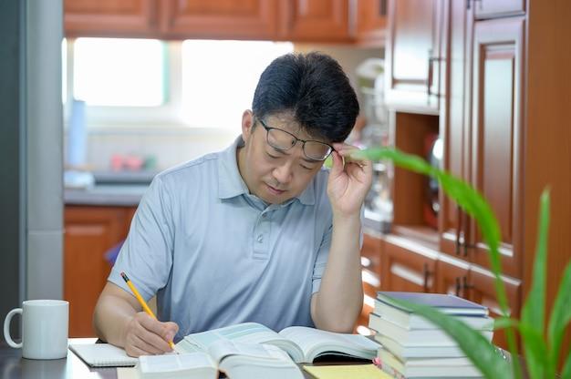 自宅の机に座って本を読んだり勉強したりしているアジアの中年男性。