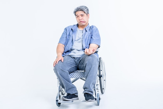 Asian middle aged man sitting on a wheelchair his hands are kinking due to a nervous