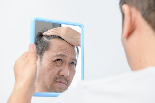 アジアの中年男性が鏡を見ていて、たくさんの顔のしわが心配でした