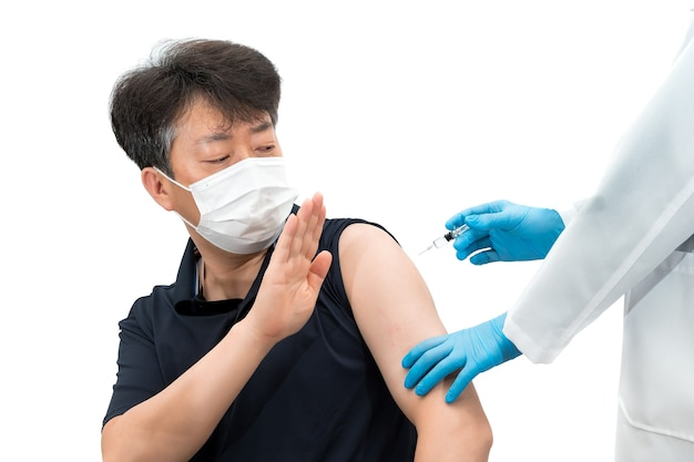 Asian middle-aged man wearing medical mask refusing to inject the vaccine.