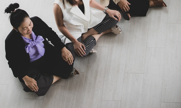 Asian middle aged and unidentified unrecognizable calm peaceful relaxation female businesswoman officer worker staffs in formal suit sitting squat resting quiet on floor practice meditation together.
