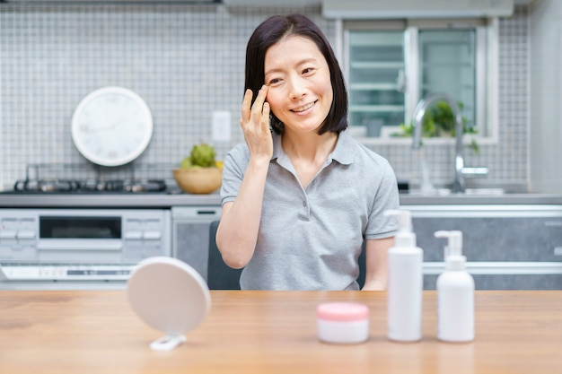 Asian middle-aged woman checking skin condition at home