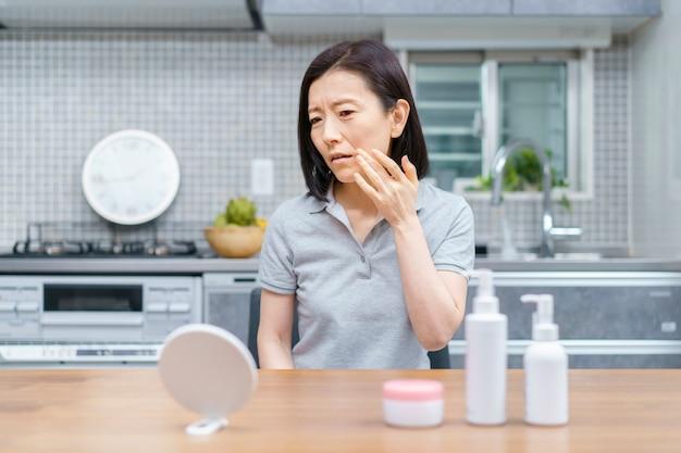 部屋で不安な表情で肌の状態をチェックするアジアの中年女性