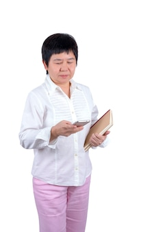 Asian middle-aged woman holding books and using mobile phone isolated on white background