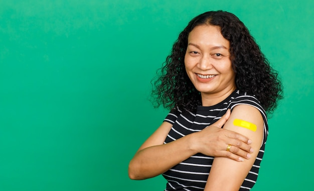 Asian middle aged woman holding her arm with bandage patch showing she got vaccinated for covid 19 virus on green background. concept for covid 19 vaccination.