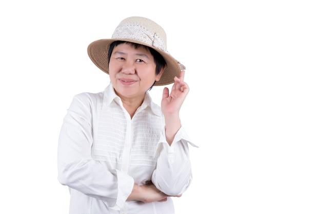 白いシャツと白い背景で隔離の編まれた帽子のアジアの中年女性