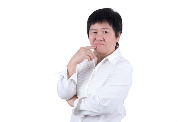 흰색 셔츠를 입은 아시아 중년 여성은 흰색 배경에 고립되어 불행하거나 불만족스럽다.