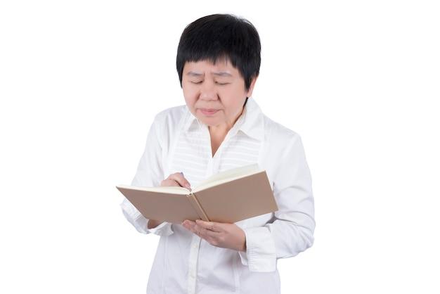 白い背景、視力の概念に分離された書き込みまたは読み取りで視力の問題を抱えている白いシャツのアジアの中年女性