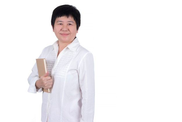 白い背景で隔離の彼女の手で本を保持している白いシャツのアジアの中年女性