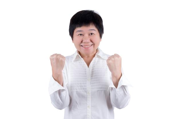 白いシャツを着たアジアの中年女性は、白い背景で隔離の何かで成功を表現する彼女の拳を上げます