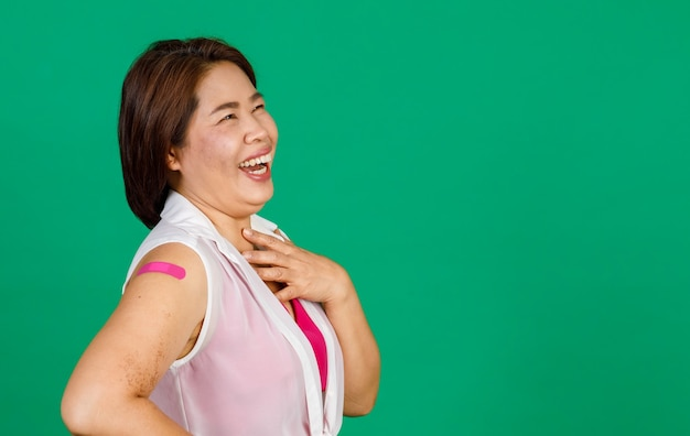 Asian middle aged woman laughing with relieved, her arm with bandage patch showing she got vaccinated for covid 19 virus on green background. concept for covid 19 vaccination.