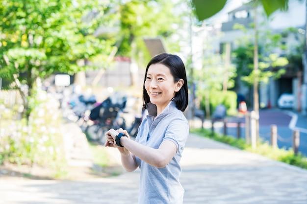屋外でスマートウォッチを操作するアジアの中年女性