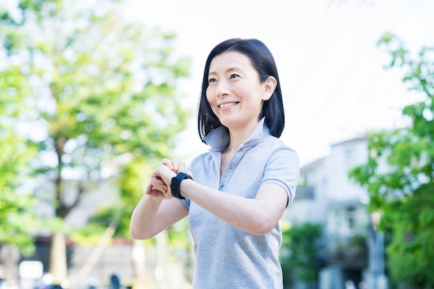 Asian middle-aged woman operating a smartwatch outdoors