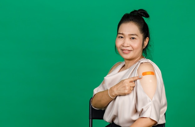 Asian middle aged woman smiling and pointing at her arm with bandage patch showing she got vaccinated for covid 19 virus on green background. concept for covid 19 vaccination.