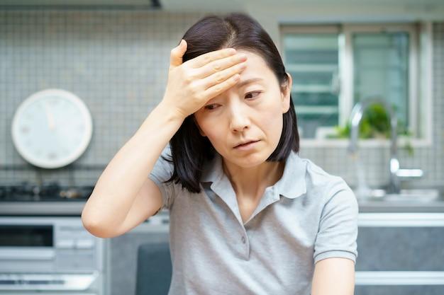 방에서 두통으로 고통받는 아시아 중년 여성