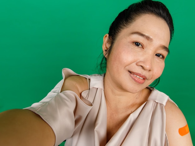 Asian middle aged woman taking selfie showing her arm with bandage patch that got vaccinated for covid 19 virus on green background. concept for covid 19 vaccination.