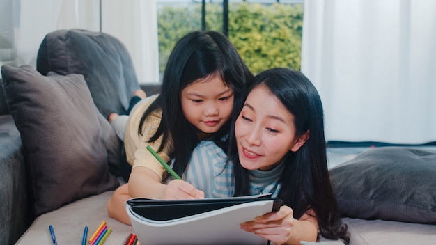 Asian middle-aged woman teach her daughter do homework and drawing at home. lifestyle mother and kid happy fun spend time together in living room in modern home in the evening .