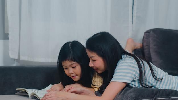 アジアの中年の女性は娘に本を読んで教え、家でくつろいで自由時間を楽しんでいます。ライフスタイルの母親と子供の幸せな楽しみは、夜に現代の家のリビングルームで一緒に時間を過ごします。