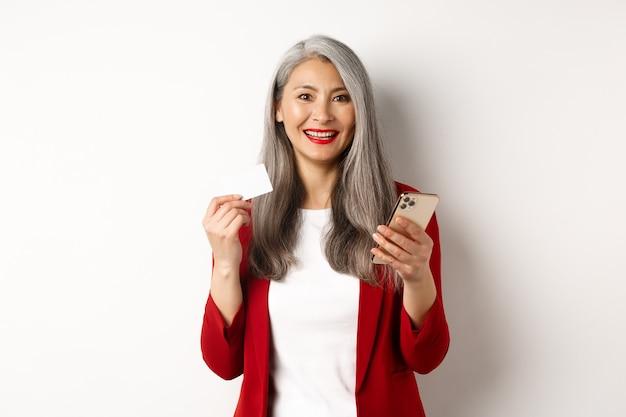 플라스틱 신용 카드와 스마트폰을 사용하여 온라인 쇼핑을 하는 아시아 중년 여성이 흰색 배경 위에 서 있습니다.