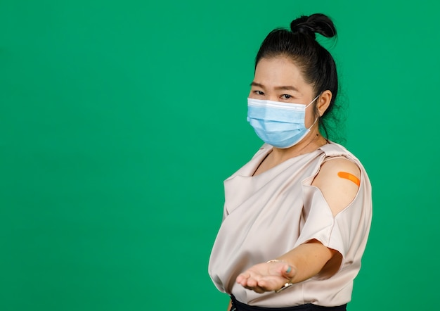 Asian middle aged woman wearing face mask her arm with bandage patch showing she got vaccinated for covid 19 virus on green background. concept for covid 19 vaccination.