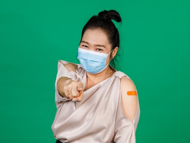Asian middle aged woman wearing face mask and pointing at camera her arm with bandage patch showing she got vaccinated for covid 19 virus on green background. concept for covid 19 vaccination.