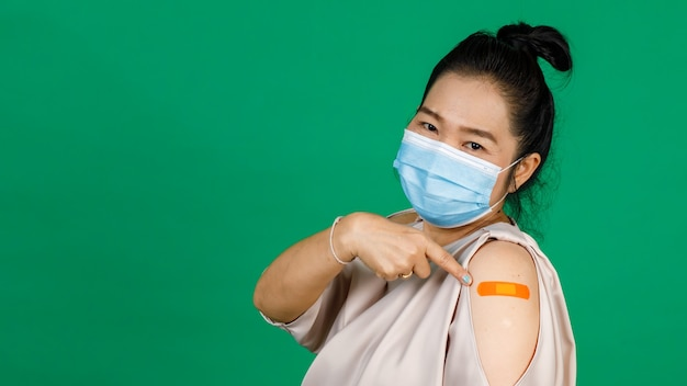 Asian middle aged woman wearing face mask and pointing at her arm with bandage patch showing she got vaccinated for covid 19 virus on green background. concept for covid 19 vaccination.
