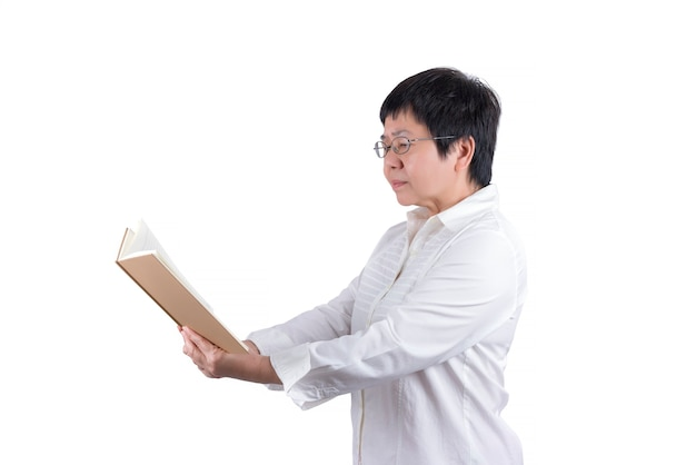 Asian middle-aged woman in white shirt wearing eyeglasses reading a book isolated on white background , eyesight concept