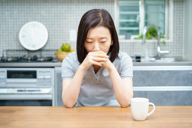 部屋で疲れた表情のアジアの中年女性