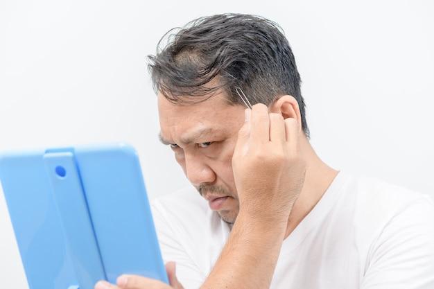 Азиатский средний мужчина смотрит в зеркало и выщипывает свои седые волосы пинцетом на белом фоне, концепция здравоохранения