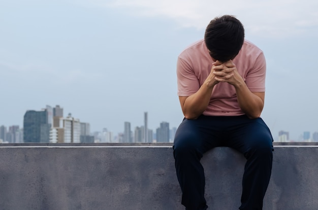 Asian miserable depressed man sit alone with city background