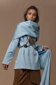 Азиатская модель позирует в синей хлопковой блузке с поясом на талии и коричневой бархатной юбке.