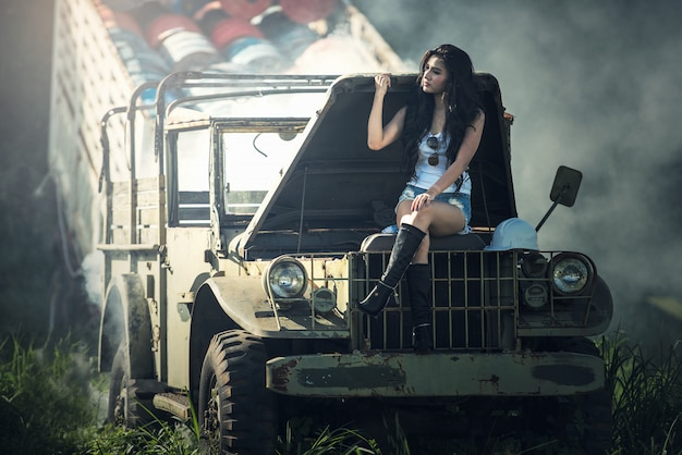 Asian model posing with old truck in an outdoor environment
