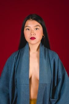 アジアのモデルが赤の背景でポーズ