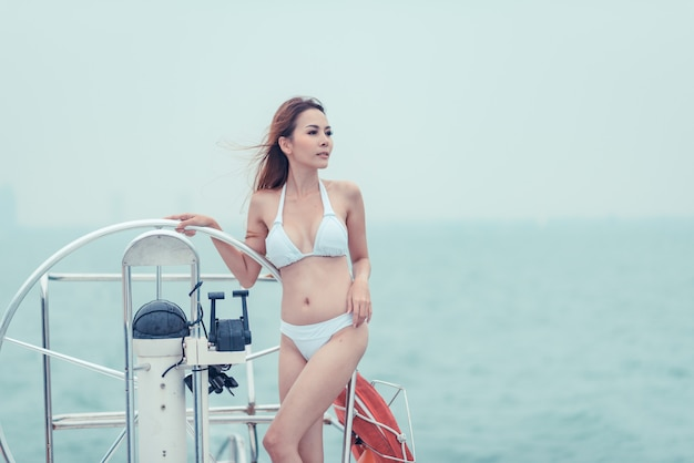 Asian model in a white bikini on a yacht