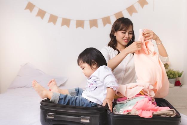 スーツケースの荷物と休暇で旅行する準備ができて服を着たアジアのママと女の赤ちゃん