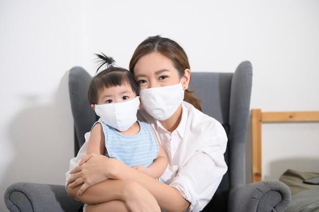 Азиатские мама и дочь носят защитную маску дома