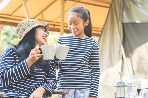 Азиатская мама и дочь наслаждаются напитком в кемпинге