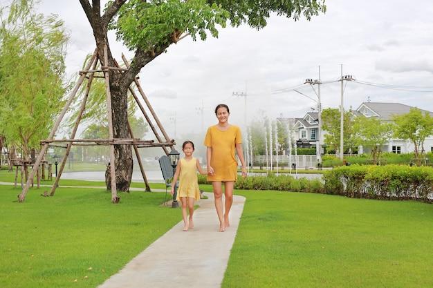 아시아 엄마와 딸 손을 잡고 정원에서 산책