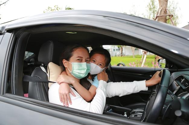 アジアのママと娘は、コロナウイルス(covid-19)の発生時にカメラを通して見ながら車の中で横たわっている衛生フェイスマスクを着用します