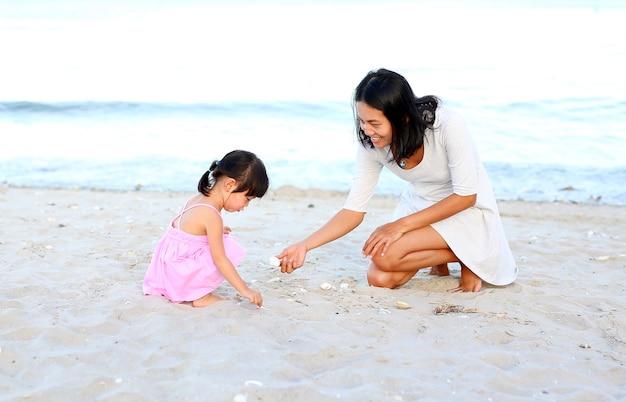 아시아 엄마와 그녀의 딸 여자 아이가 해변에서 모래놀이를 하고 있습니다. 행복한 사랑하는 가족.