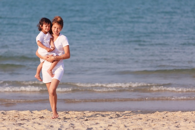 Азиатская мама и сын играют на тропическом пляже