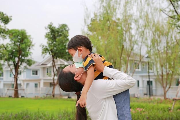 코로나바이러스와 독감 발병 기간 동안 보호용 안면 마스크를 착용하고 공공 정원에서 키스를 한 아들을 안고 있는 아시아 엄마