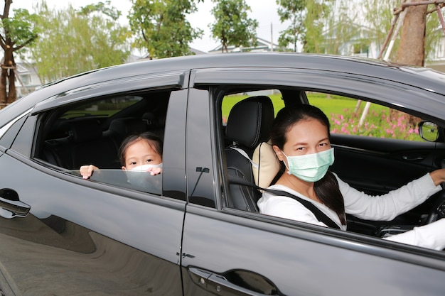 Asian mom and daughter wears hygiene mask lying in car with looking through camera
