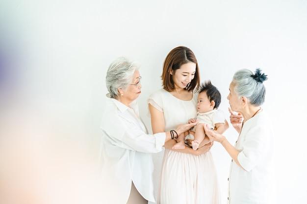 赤ちゃんと2人の年配の女性を保持しているアジアのお母さん