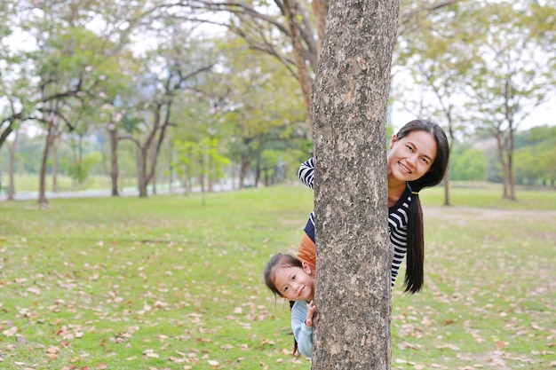 Asian mom and little girl hide body behind tree in garden.